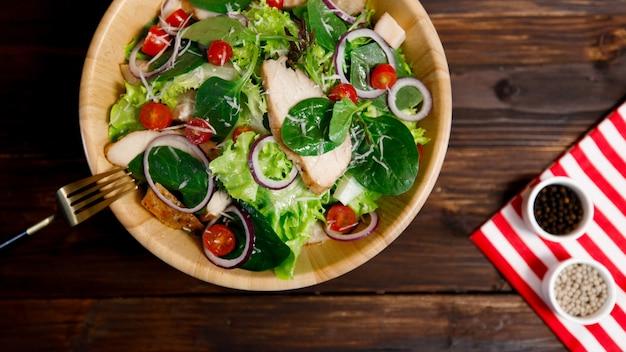 Photo d'angle de vue de dessus de poitrine de poulet grillée salade de légumes frais et filets avec une variété de sortes de légumes naturels dans un bol en bois sur fond de bois. idée de menu sain et diététique.
