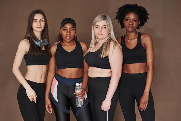 Photo après un entraînement intensif. groupe de femmes multiethniques debout contre l'espace brun