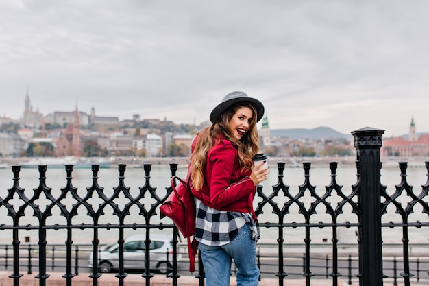 Photo de l'arrière d'une femme brune excitée en chemise à carreaux profitant de la vue sur la rivière