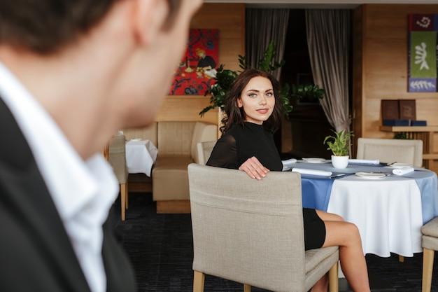 Photo de l'arrière d'un homme rencontrant une femme dans un restaurant