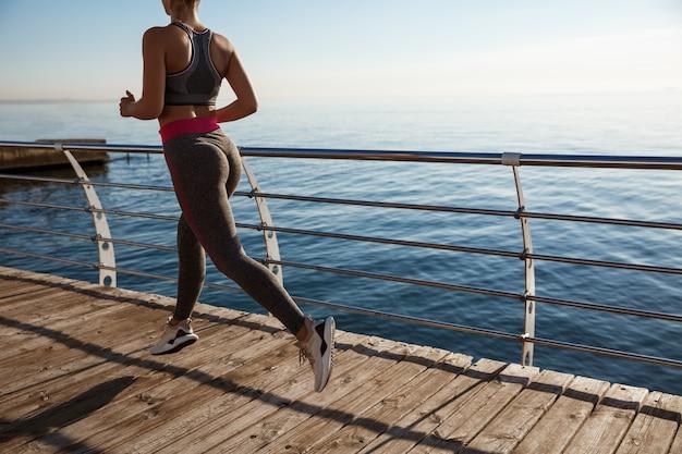 Photo arrière recadrée d'une femme fitness faisant du jogging sur une jetée, séance d'entraînement seule.
