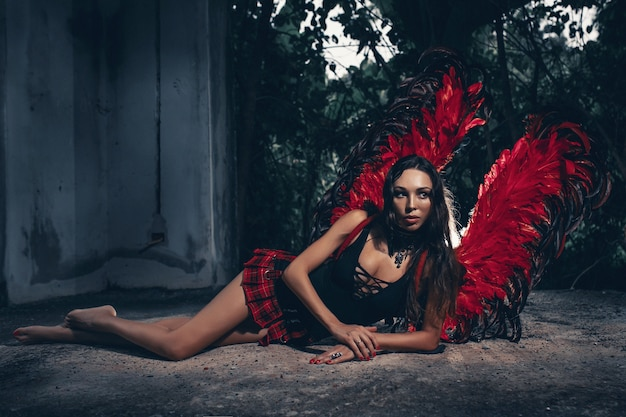 Photo d'art d'une belle femme dark angel. une fille avec des ailes de diable rouge et une robe noire dans la chambre noire