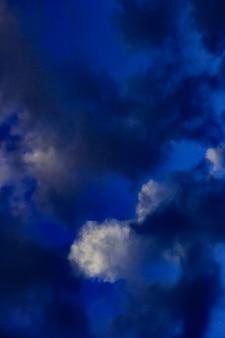 Photo artistique du ciel avec des nuages dans des couleurs bleu foncé et blanc, conception de fond de nature abstraite