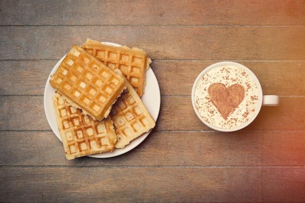 Photo d'une assiette pleine de gaufres et d'une tasse de café sur le magnifique fond en bois marron