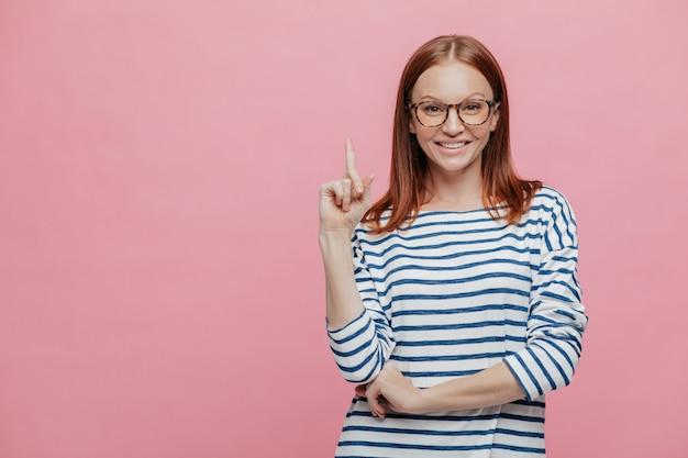 Photo d'une assistante souriante au magasin, vêtue d'un pull rayé et gardant le doigt levé vers le haut