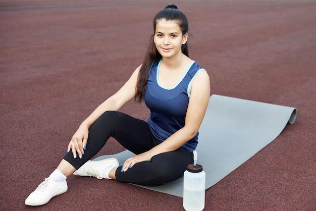 Une photo d'une athlète féminine heureuse tenant une bouteille d'eau et assise sur un tapis de yoga.