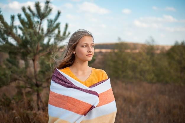 Photo atmosphérique d'une jeune fille en plaid debout dans le domaine