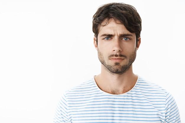 Photo authentique d'un petit ami contrarié qui boude et fronce les sourcils alors qu'une femme déçue a oublié de féliciter avec un anniversaire debout sombre et malheureux contre un mur gris en t-shirt rayé