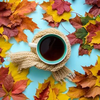 Photo d'automne avec une tasse de thé dans une écharpe en feuilles d'automne