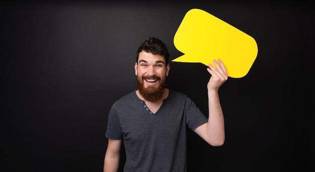 Photo de barbu tenant un discours de bulle jaune debout sur fond sombre