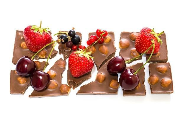 Photo de barre cassée de chocolat avec des noix et des baies sur fond blanc isolé
