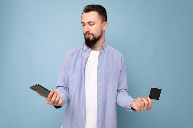 Photo de beau bouleversé attrayant brunet mal rasé jeune homme portant une chemise bleue décontractée et blanc