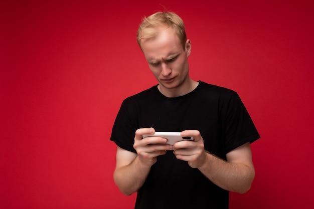 Photo de beau concentré bouleversé insatisfait jeune homme blond isolé sur fond rouge mur