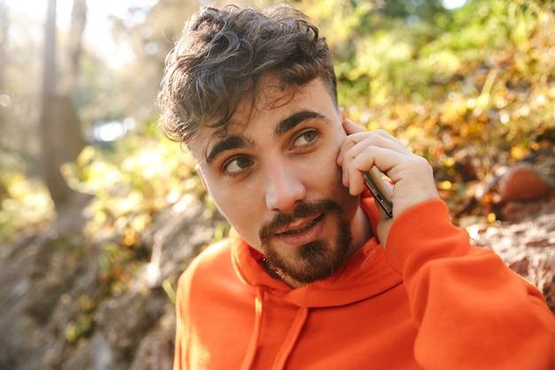 Photo de beau coureur d'homme de remise en forme sportif jeune heureux à l'extérieur dans le parc, parler par téléphone mobile.