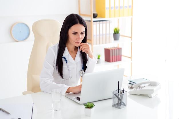 Photo de beau docteur femme sérieuse s'asseoir ordinateur portable