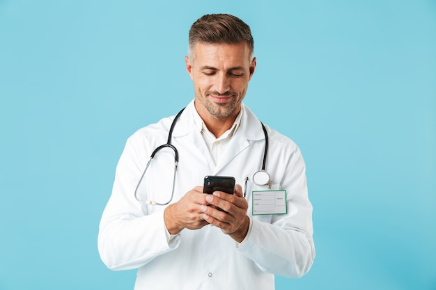 Photo de beau docteur en médecine portant blouse blanche et stéthoscope tenant le smartphone, debout isolé sur mur bleu