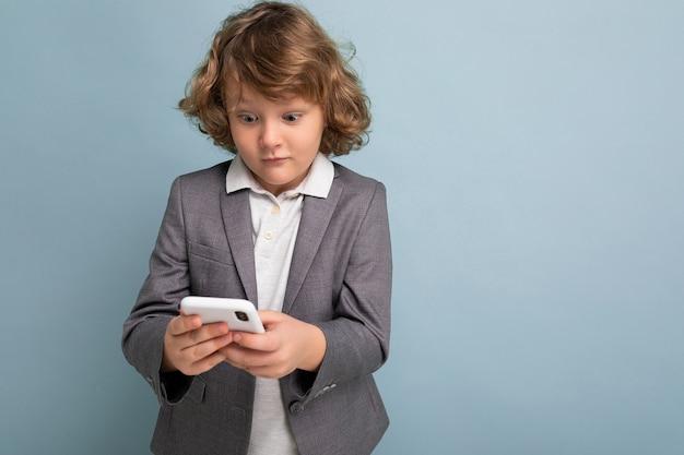 Photo d'un beau garçon surpris aux cheveux bouclés portant un costume gris tenant et utilisant un téléphone isolé