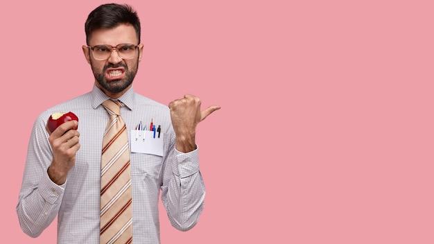 Photo de beau gestionnaire masculin expérimenté sourit, serre les dents, mécontent et en colère, porte une tenue élégante