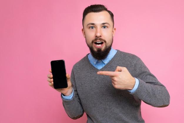 Photo d'un beau homme adulte souriant beau portant une tenue décontractée debout isolé sur fond avec espace de copie tenant un smartphone montrant le téléphone à la main avec un écran vide pour mo