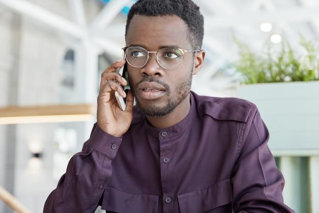 Photo de beau homme sérieux à la peau foncée résout au cours d'une consultation téléphonique, tente d'expliquer son idée, parle avec le support client