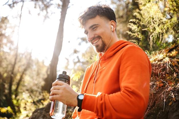 Photo de beau jeune coureur de fitness sport homme à l'extérieur dans l'eau potable du parc.