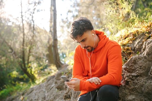 Photo de beau jeune coureur de fitness sport homme à l'extérieur dans le parc, écouter de la musique avec des écouteurs à l'aide de téléphone mobile.
