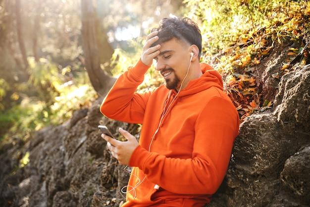 Photo de beau jeune coureur d'homme de remise en forme sportif heureux à l'extérieur dans le parc, écouter de la musique avec des écouteurs à l'aide de téléphone mobile.