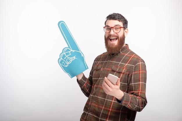 Photo de beau jeune homme applaudir avec des gants de mousse et de football, jeu en ligne