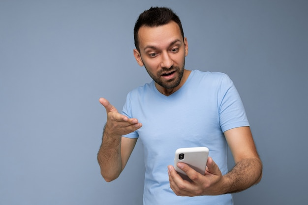 Photo de beau jeune homme à la barbe portant un t-shirt bleu de tous les jours isolé sur fond bleu
