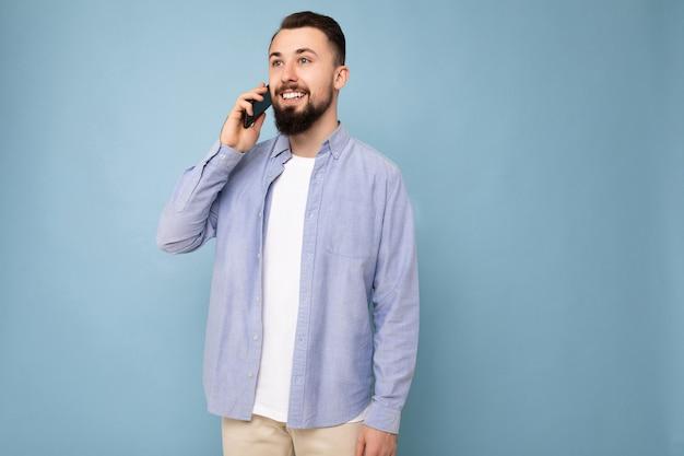 Photo d'un beau jeune homme barbu brun portant une chemise bleue décontractée et un t-shirt blanc