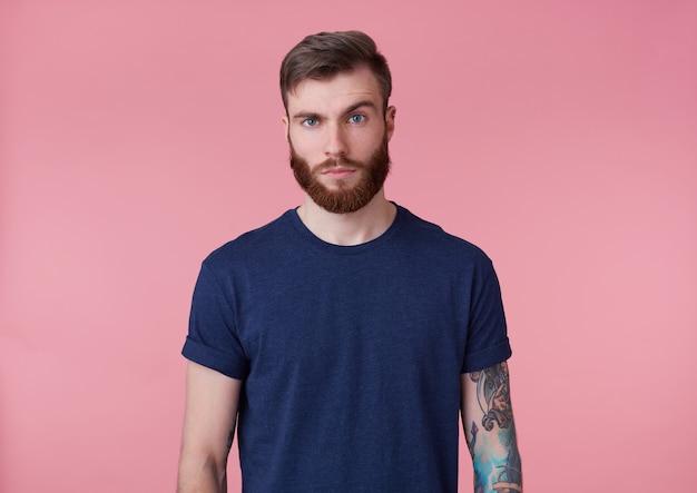 Photo de beau jeune homme barbu tatoué malentendu en t-shirt blanc, se dresse sur fond rose, regarde la caméra avec un sourcil levé.