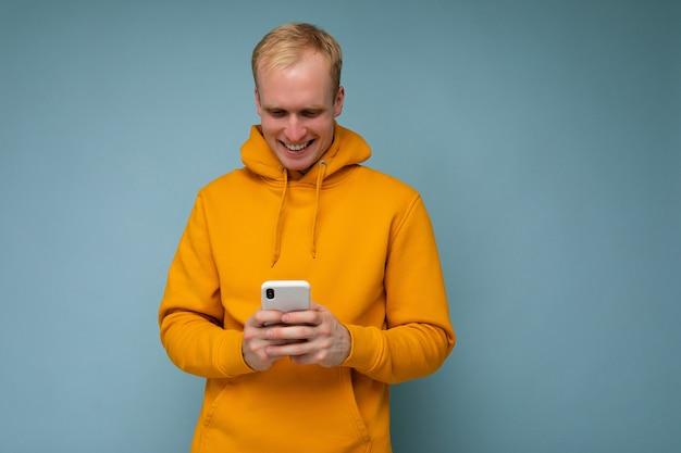 Photo d'un beau jeune homme blond positif et beau portant un sweat à capuche jaune en équilibre isolé sur fond avec un espace vide tenant dans la main et utilisant des sms de messagerie de téléphone portable regardant smar