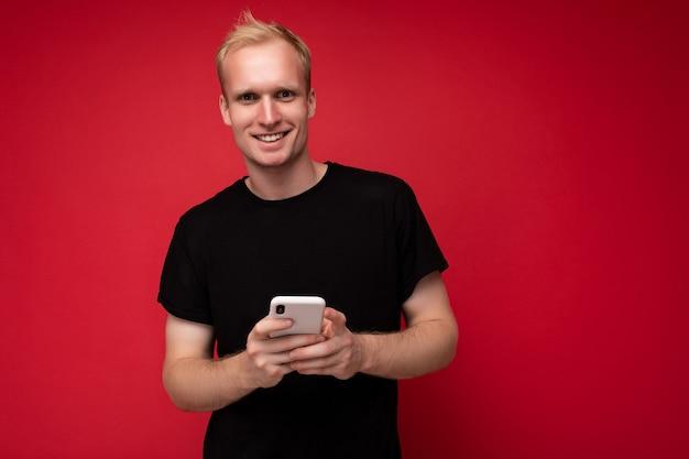 Photo d'un beau jeune homme blond positif souriant isolé sur un mur de fond rouge portant un t-shirt noir tenant et utilisant un téléphone portable en écrivant des sms en regardant la caméra.