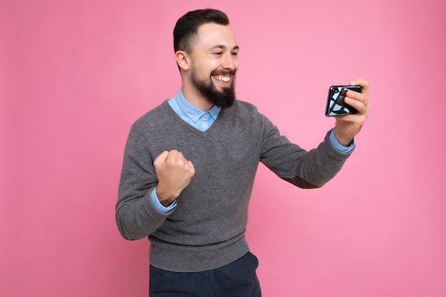 Photo d'un beau jeune homme mal rasé avec une barbe portant un pull gris et bleu tous les jours