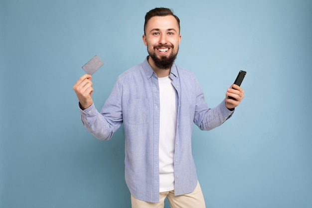 Photo d'un beau jeune homme non rasé brunet souriant portant une chemise bleue décontractée et