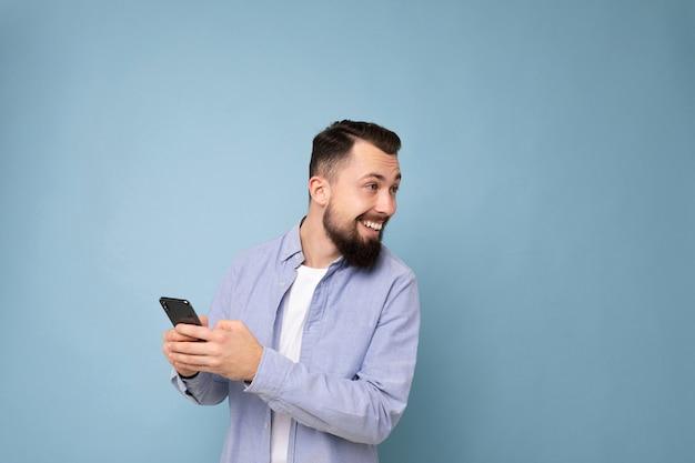 Photo d'un beau jeune homme positif et beau portant une tenue élégante et décontractée, isolé sur fond avec un espace vide tenant dans la main et utilisant des sms de messagerie de téléphone portable regardant derrière