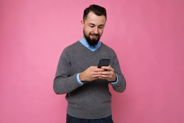 Photo d'un beau jeune homme positif et beau portant une tenue élégante et décontractée en train de se poser