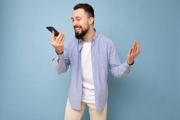Photo d'un beau jeune homme positif et beau vêtu d'une tenue élégante et décontractée, isolé sur fond avec un espace vide tenant dans la main et utilisant un téléphone portable enregistrant un message vocal