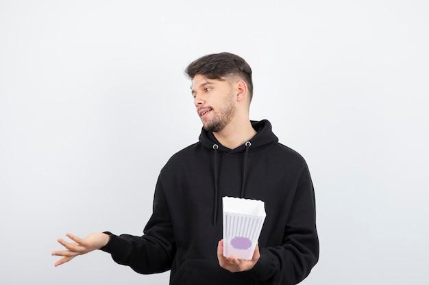 Photo de beau jeune homme regardant des séries télévisées et tenant un seau de pop-corn