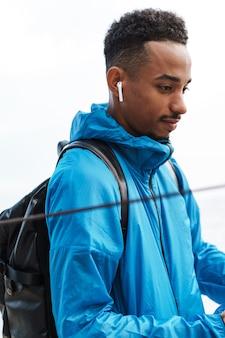 Photo d'un beau jeune homme sportif africain à l'extérieur à la plage mer marchant avec sac à écouter de la musique avec des écouteurs.