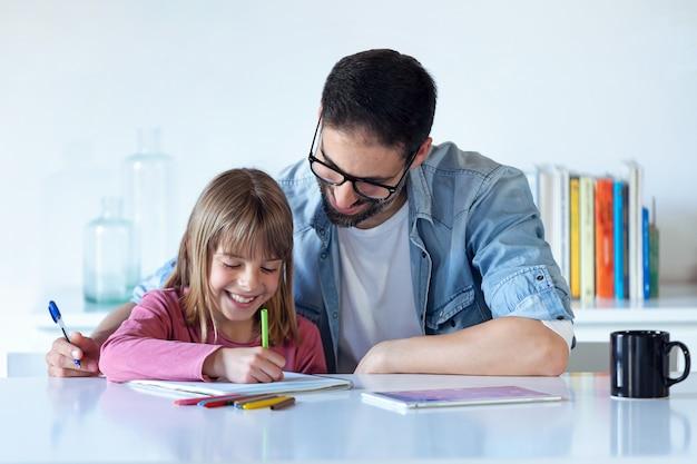 Photo d'un beau jeune père avec sa fille dessinant sur un ordinateur portable à la maison.