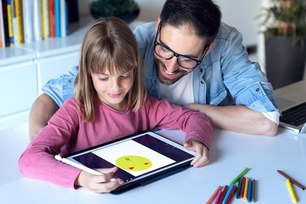 Photo d'un beau jeune père avec sa fille dessinant avec une tablette numérique à la maison.