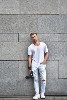Photo d'un beau mec caucasien sur un mur texturé gris en t-shirt blanc et jean blanc avec caméra accrochée à la sangle sur son bras.