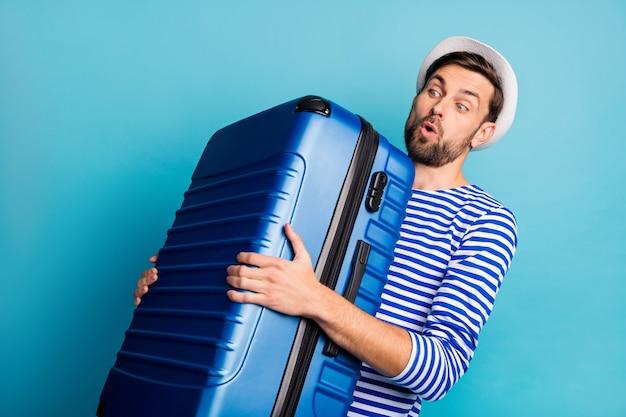 Photo de beau mec voyageur tenir grosse valise avion vol allocation de poids trop lourd sac sentir mal de dos porter chemise marin rayé gilet panama couleur bleu isolé