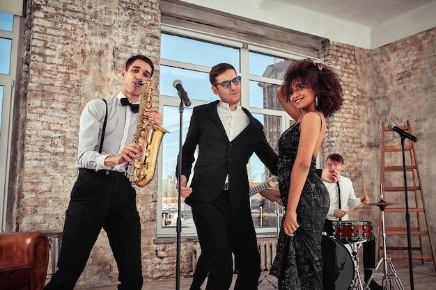 Photo de beaucoup de groupe musical ethnique en studio. des musiciens et une femme afro-américaine soliste posant devant la caméra, lors d'une répétition, arrière-plan loft.