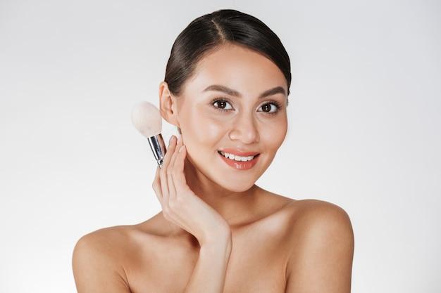 Photo de beauté d'une femme magnifique avec des cheveux en chignon à la recherche sur l'appareil photo et tenant un pinceau de maquillage, isolé sur blanc