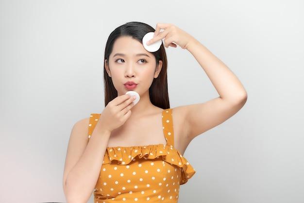 Photo de beauté d'une jeune femme nettoyant son visage avec un coton isolé sur fond blanc