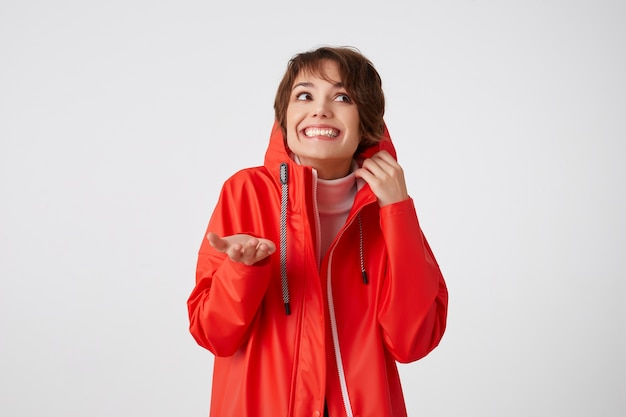 Photo de beauté jeune femme souriante aux cheveux courts en manteau de pluie rouge, regardant vers la gauche, se cache dans le capot, met la paume sous la pluie.