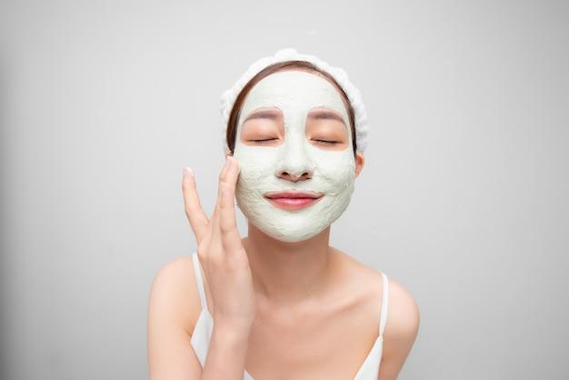 La photo de beauté d'une jolie fille asiatique avec une belle peau montre une crème de masque sur son visage sur fond blanc.