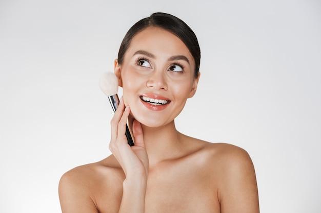 Photo de beauté de jolie jeune femme aux cheveux en chignon regardant vers le haut et tenant le pinceau de maquillage près de son visage, isolé sur blanc